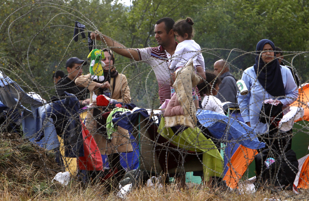 A migrant holding a child hangs up a stuffed toy to dry from the rain on the barbed wire, while waiting to enter Macedonia from Greece on the border line between the two countries, near the southern Macedonia's town of Gevgelija, on Saturday, Aug. 22, 2015. About 39,000 people, mostly Syrian migrants, have been registered as passing through Macedonia in the past month, twice as many as the month before. They previously encountered little resistance at the border, but the recent influx has overwhelmed Macedonian authorities who this week declared a state of emergency and stopped many from crossing. (AP Photo/Boris Grdanoski)