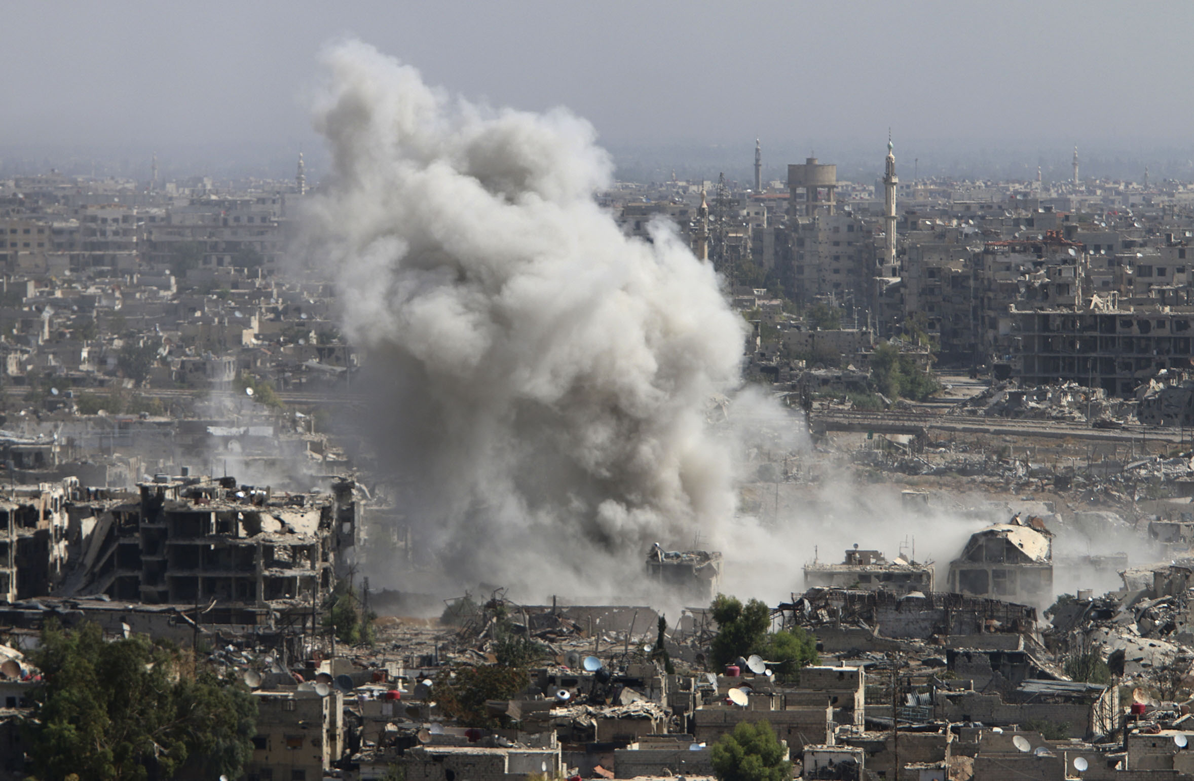 In this photo taken on Wednesday, Oct. 14, 2015, smoke rises after shelling by Syrian army in Jobar, Damascus, Syria. Backed by Russian airstrikes, the Syrian army has launched an offensive in central and northwestern regions.  (Alexander Kots/Komsomolskaya Pravda via AP) RUSSIA OUT